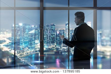 Side view of young businessman using cellphone against panoramic window with illuminated night city view