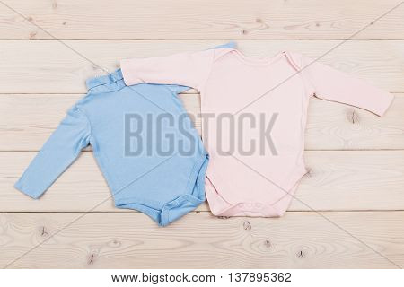 Baby girl and baby boy clothes on light wooden table. Top view Mock up