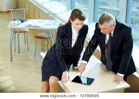 Boss pointing at screen during explanation of something to secretary