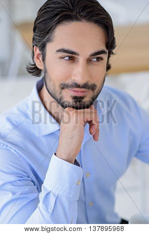 Smart young businessman dreaming about future career. He is sitting and looking aside slyly