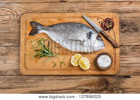 Top view of fresh dorado fish with spices on wooden cutting board.