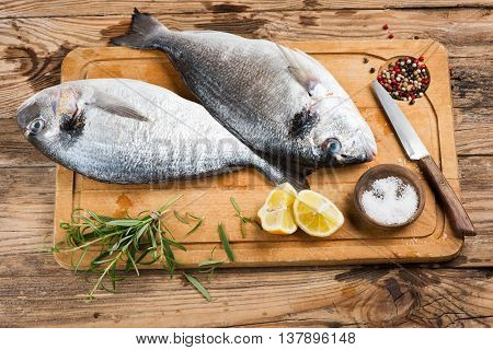 Uncooked fresh dorado fishes with spices on wooden cutting board.