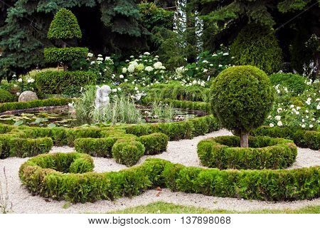 Background of garden design. Landscaping in park with pond, shorn trees and lawn