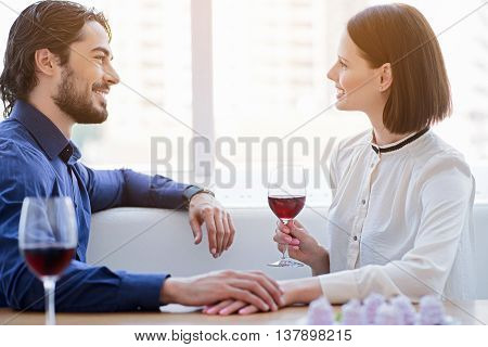I love you. Joyful man and woman have romantic dinner. They are holding hands and smiling with happines. Lovers are sitting and drinking wine