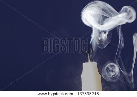 Extinguished candle with smoke on dark blue background