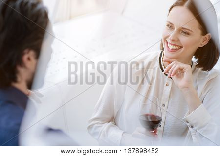 Cheerful young loving couple is dating and smiling. Woman is sitting and drinking wine. She is looking at man happily