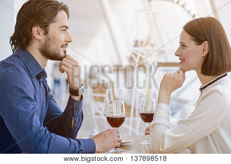 Falling in love. Attractive man and woman are flirting and smiling. They are looking at each other while drinking wine. Lovers are sitting at table in restaurant