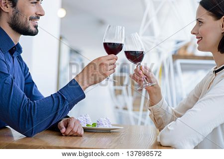 Cheers. Pretty loving couple is clinking wineglasses. They are sitting at table in restaurant and smiling