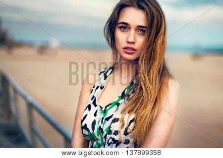 Portrait of beautiful blonde young girl with cute face looking into the camera standing outdoors near ocean beach at sunset time