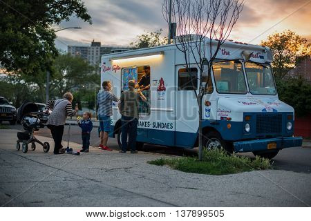 NEW YORK CITU, USA - JUNE 15, 2016: Vintage ice cream van car serving ice cream to the street customers. Man selling ice cream to people from car window