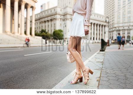 Beautiful long female legs. Beautiful woman standing on city street wearing fashionable summer outfit. Girl on high heels white skirt pink t-shirt holding clutch bag.