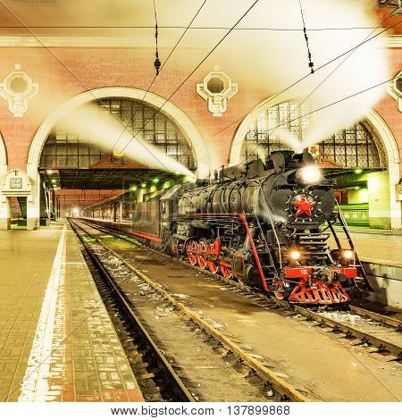 Moscow Russia - January 04 2015: Interior of Moscow railway station (Kazanskyj vokzal) and steam locomotive at winter evening time.