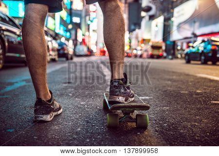 Man riding on skateboard in New York City street at the night. Male legs with skateboard in night city.