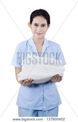 Portrait of a maid woman holding towels and smiling at camera. Isolated on white background