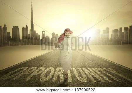 Arabian young worker running on the street while wearing islamic clothes with Opportunity word