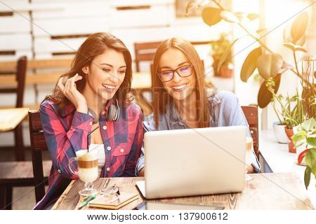 Enjoying coffee and free wifi. Two smiling young women looking at something on laptop in coffee shop
