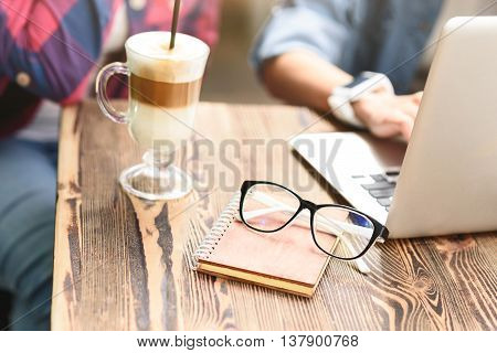 Having some coffee with my best friends. Close up of glasses lying with notepad on wooden table in coffee shop next to glass of latte