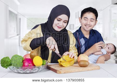 Portrait of two parents and little son with fresh fruits and vegetable on desk in the dining room