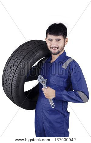 Portrait of Arabian mechanic smiling at the camera while wearing uniform and holding a spanner with tire