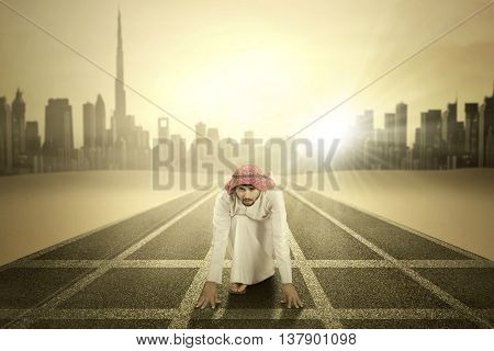 Portrait of Arabic young businessman kneeling on the road and ready to race