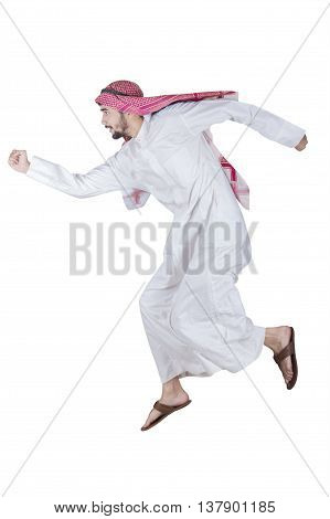 Picture of Arabic young man running in the studio while wearing islamic clothes isolated on white background