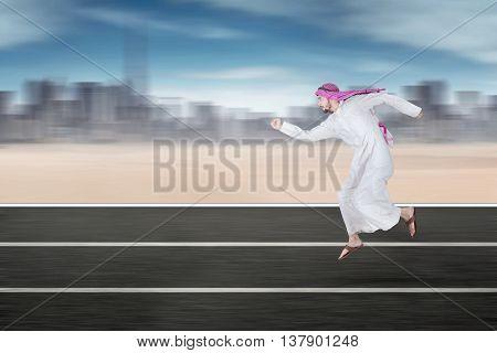 Portrait of Arabic businessman running on the highway