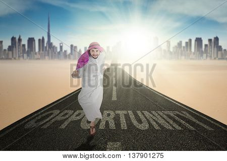 Picture of Arabic worker running on the highway with Opportunity word and wearing islamic clothes