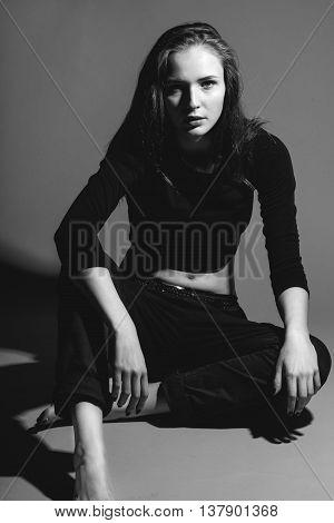 Fashionable Woman Sitting On Studio Floor, Monochrome Photography