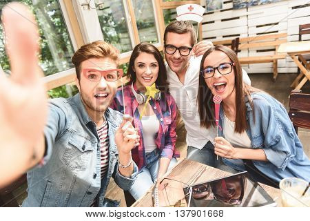 Giving happy smiles. Close up of four friends spending time in coffee shop and making selfie, using mobile phone
