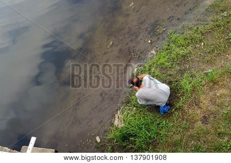 SHOREWOOD, ILLINOIS / UNITED STATES - AUGUST 30, 2015: A man fishes in a small lake in the Towne Center Park, adjacent to the Village of Shorewood Village Hall.