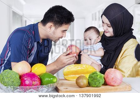 Portrait of two happy parents giving healthy food to their baby in the dining room