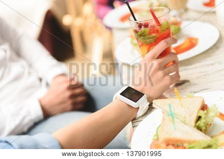 Everything must be at time. Close up of hand holding glass with cocktail and wearing smart watch on wood table during lunch