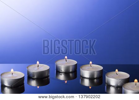 Lit Tea Candles with Reflection on Blue background