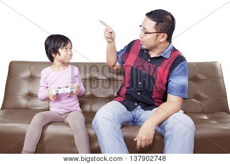 Young man scolding his daughter to stop playing video game while sitting on the sofa