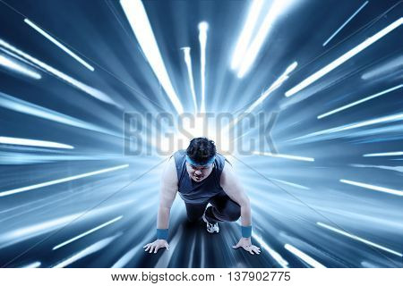 Overweight person ready to run and workout with fast motion blur background