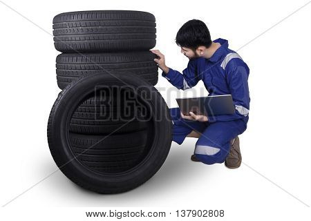Arabian mechanic checking tires while wearing uniform and holding a laptop computer isolated on white background