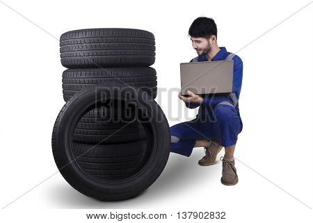 Male mechanic holding a laptop computer while checking tires isolated on white background