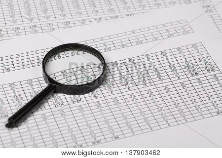 Conceptual photo of Magnifying Glass on Reports with figures