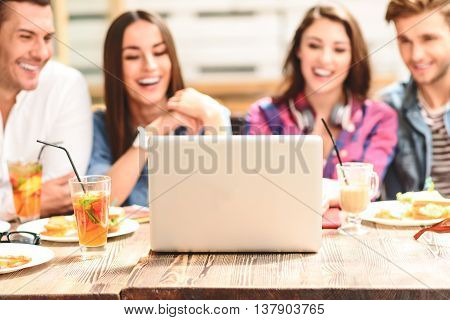 Sharing some time online. Close up of laptop standing on wooden table with cheerful four smiling friends in background