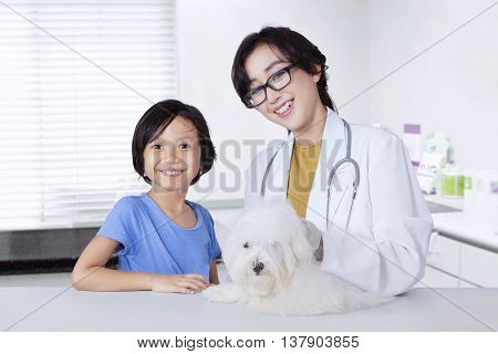 Portrait of young veterinarian and little girl smiling at camera with a dog on the desk in the clinic