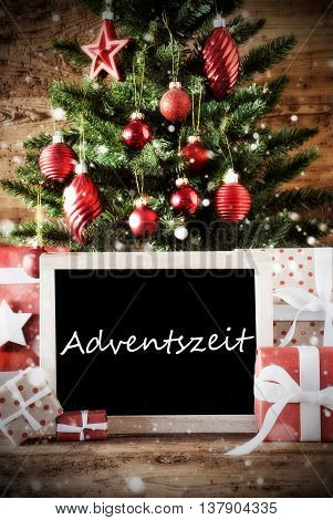Christmas Card For Seasons Greetings. Christmas Tree With Balls. Gifts Or Presents In The Front Of Wooden Background. Chalkboard With German Text Adventszeit Means Advent Season