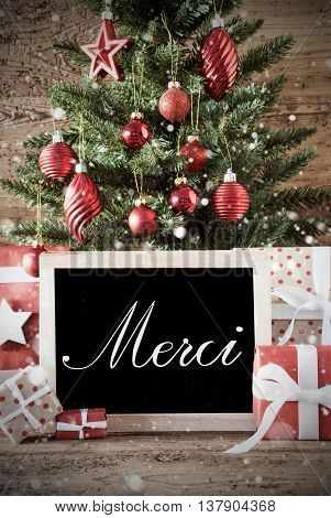 Nostalgic Christmas Card For Seasons Greetings. Christmas Tree With Balls. Gifts Or Presents In The Front Of Wooden Background. Chalkboard With French Text Merci Means Thank You