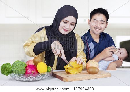 Two happy parents and their little son cooking with fruits on the table. Shot in the kitchen at home