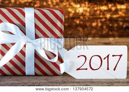 Macro Of Christmas Gift Or Present On Atmospheric Wooden Background. Card For Seasons Greetings, Best Wishes Or Congratulations. White Ribbon With Bow. Text 2017 For Happy New Year