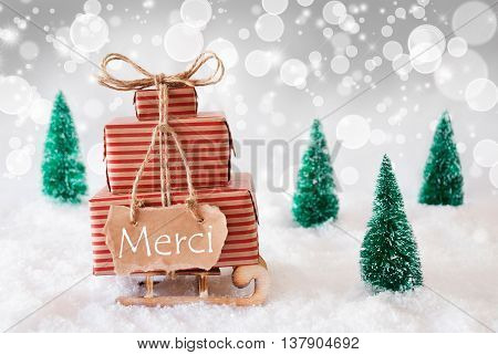 Sleigh Or Sled With Christmas Gifts Or Presents. Snowy Scenery With Snow And Trees. White Sparkling Background With Bokeh Effect. Label With French Text Merci Means Thank You