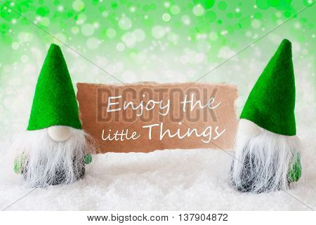 Christmas Greeting Card With Two Green Gnomes. Sparkling Bokeh And Natural Background With Snow. English Quote Enjoy The Little Things