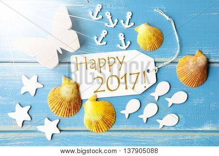 Flat Lay View Of Label With English Text Happy 2017. Sunny Summer Greeting Card. Butterfly, Shells And Fishes On Blue Wooden Background