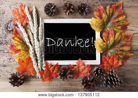Blackboard With Autumn Or Fall Decoration. Greeting Card For Seasons Greetings. Colorful Leaves, Fir Cone And Barley On Aged Wooden Background. German Text Danke Means Thank You