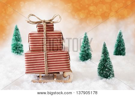 Sleigh Or Sled With Christmas Gifts Or Presents. Snowy Scenery With Snow And Trees. Orange Background With Bokeh Effect.