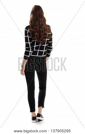 Woman in black checkered sweater. Back view of skinny pants. Trendy autumn look. Casual apparel from new catalog.